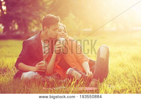 A loving couple of teenagers. Sudden picnic in the park at sunset. Teens drink soft drinks sitting on the lawn. He hugs her shoulders. She smiles.