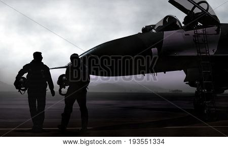 Pilots with a jet fighter on military airbase at dawn