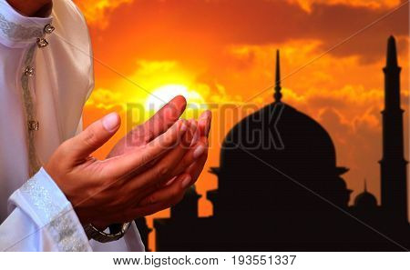 Praying hands with a mosque in sunset background
