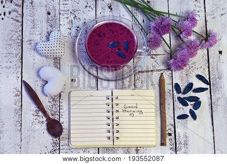 Top view of honey berry smoothie, wildflowers, spoon, heart decorations and open diary with text good morning on white planks. Morning still life with healthy breakfast, vegetarian and vegan concept