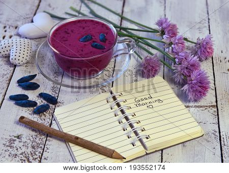 Open diary with good morning text and glass cup of honey berry smoothie on planks. Morning still life with healthy breakfast. Beautiful summer vintage background, vegetarian and vegan concept