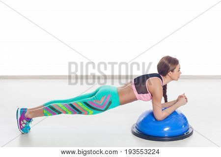 Young athletic woman doing exercise on bosu. Training yoga pilates. gym