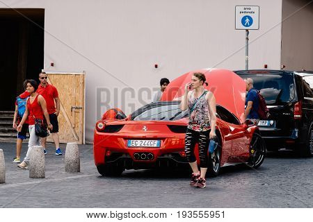 Rome Italy - August 18 2016: Tourists with luxury sport car for rental in Piazza del Popolo a sunny day of summer.