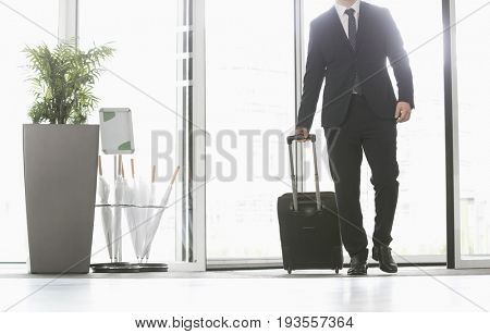 Businessman with luggage entering convention center
