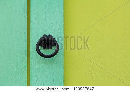 Front view of metal antiques style door handle on wood panel with paint wall two toned green color.