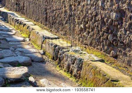 Raised pavement along the stone walls in a street of Pompeii - Campania Italy