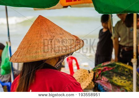 Muine Vietnam - May 26 2017: Unidentified Woman Wearing A Traditional Hat Shopping In The Seafood Fresh Market At Muine Pier In Muine Vietnam.