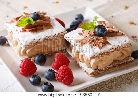 Chocolate Millefeuille With Coffee Cream, Raspberries And Blueberries Close-up. Horizontal