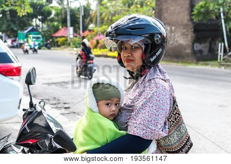 BALI, INDONESIA - JUNE 2, 2017: Portrait of balinese mother with her children in hands sitting on the motorbike.