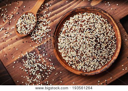 Mixed quinoa in bowl on wooden kitchen board top view. Flat lay.
