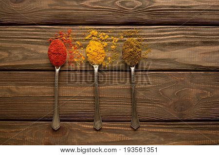 Spice. Spice powder on a wooden background. Three spoons with various spices.