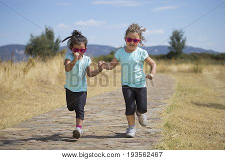 Portrait of little girls in similar wear running holding hand in hand along stone path in park in sunlight.