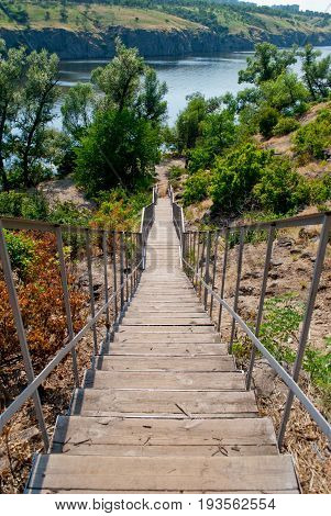 A wooden long staircase with metal railings leads downwards against the background of the nature of the Ukrainian river Dnieper and the shores of the forest on a summer day