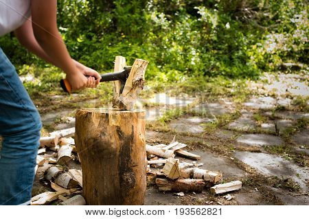 Young Man With Axe Chopping Wood On A Chopping Block