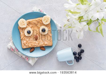 Peanut butter toast with banana, almonds and blueberries on a blue plate shaped as cute little owl. Breakfast for kids, food art concept. Table top view