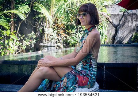 Young sexy woman in a beautful dress near the swimming pool on a luxury villa.