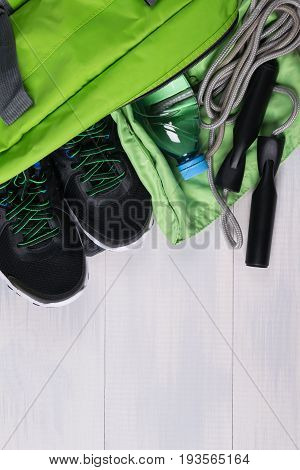 Green things for sports in bags lie on the gray floor