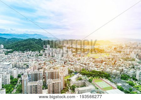 Asia Business concept for real estate and corporate construction - panoramic modern cityscape building bird eye aerial view with green mountain under sunrise and morning blue bright sky shot in Taipei 101 Taiwan