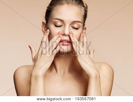 Beautiful young girl touching her clean skin face. Portrait of sensual girl with perfect make up on beige background. Youth and skin care concept