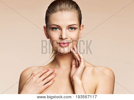 Perfect young girl with beautiful make up looks at the camera. Photo girl of european appearance on beige background. Youth and skin care concept
