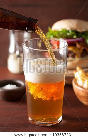 pouring india pale ale beer into pint glass and fast food