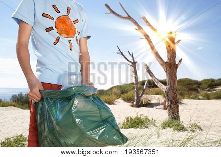 Midsection of young boy carrying plastic bag filled with garbage on beach