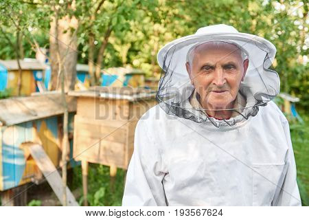 Happy senior man wearing beekeeping suit smiling to the camera posing at his apiary copyspace seniority old profession retirement retired happiness farming.