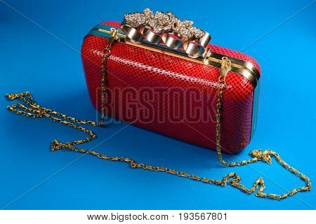 Red Handbag Clutch With Chain On Blue Background
