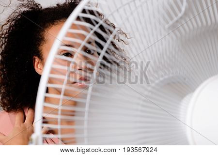 Black woman feeling hot and sitting in front of an electric fan