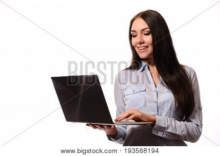 Happy attractive young woman in denim shirt standing and looks screen laptop over white background