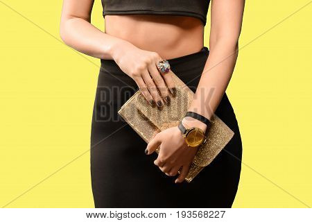 Trendy young girl in black skirt holding golden leather handbag yellow background