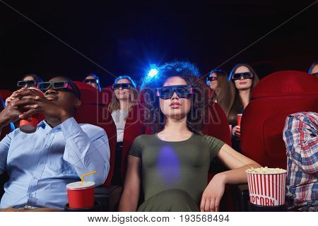 Gorgeous young woman watching a 3D movie sitting relaxed at the cinema entertainment activity leisure hobby technology enjoyment recreation concept.