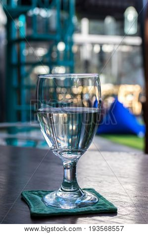 Glass of water on a wooden table in a restaurant.