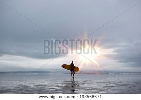 Full length of young male surfer with surfboard walking towards sea on beach