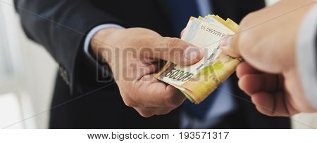 Businessman giving money South Korean won banknotes to his partner bribery concept - panoramic banner