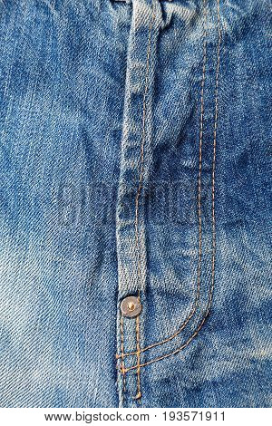 Buttoned zipper on old blue jeans. Background and texture