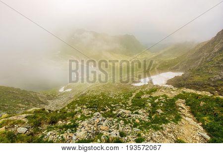 Steep on rocky hillside over balea lake in fog. mystic weather in romanian mountains