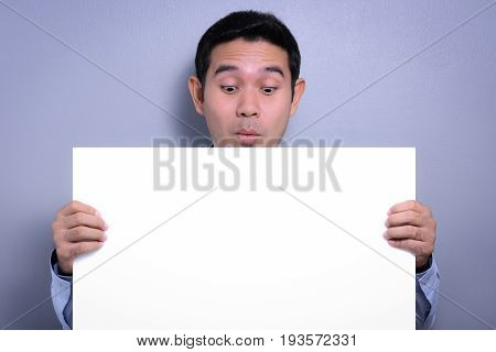 Empty white paperboard held by a man with surprised face