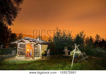 Old hut in the mountains at night under the stars. Candlelight illuminates the interior of the log cabin. Alternative lifestyle with freedom and independence.