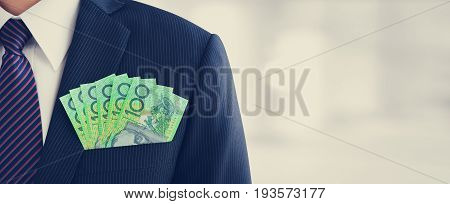 MoneyAustralian dollar (AUD) banknotes in businessman suit pocket - financial and investment panoramic background with copy space