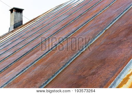 Metal roof and chimney with rusted and corroded surface. Grungy texture and background.