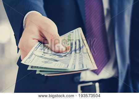 Businessman giving money united states dollar (USD) bills - cash payment and financial concepts