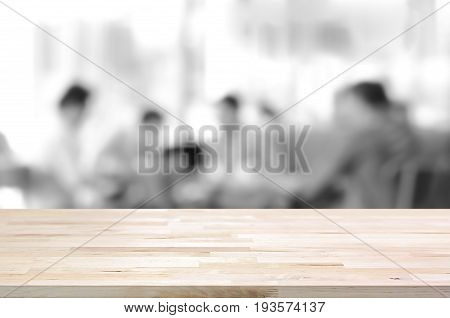 Wood table top on blurred monochrome background of people sitting in cafe - can be used for montage or display your products
