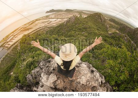 Funny female traveler with hat sitting on top of a mountain and enjoying , freedom viewpoint of Thailand.