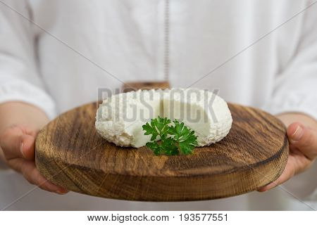 Closeup of woman's hand holding round white homemade cheese - traditional milk creamy dairy product on vintage wooden board. Rustic style.