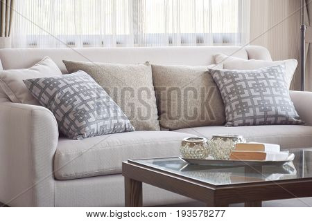 Pattern pillows setting on beige sofa in warm living room
