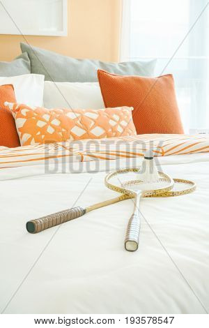 Orange Color Scheme Bedding With Rackets And Shuttlecock On Bed At Home