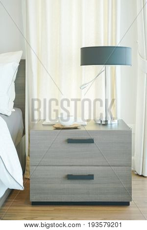 Closeup Wooden Night Table With Reading Lamp, Coffee Cup And Book In Modern Bedroom