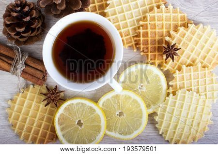 Cup of black tea with Christmas decor, lemon, pinecone, waffles, badian and cinnamon.