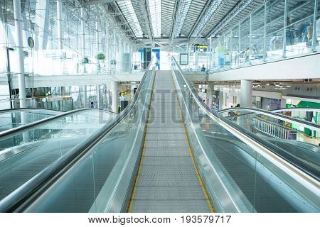 long escalator in modern airport building in cold tone